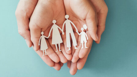adult hands holding child hands holding paper family cutout