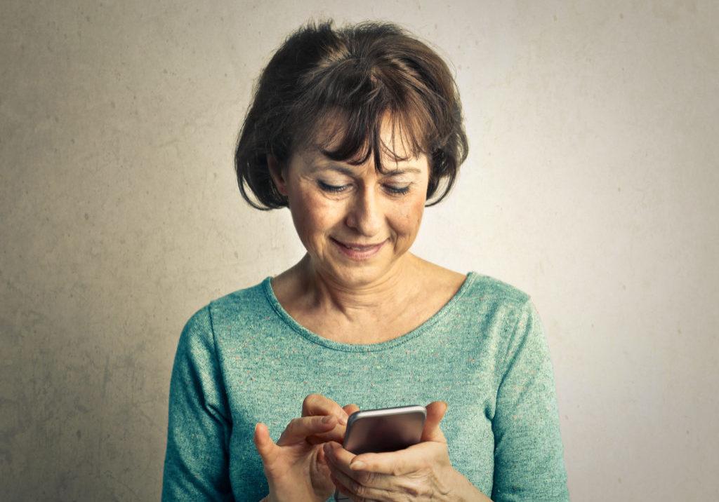 Canva - Elderly Woman in Green Long Sleeve Shirt is Having Fun Using Smartphone